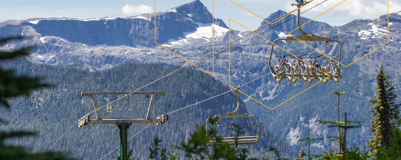 Mount Washington Resort ski lifts bringing up mountain bikes with a view of snow capped mountains in the background.