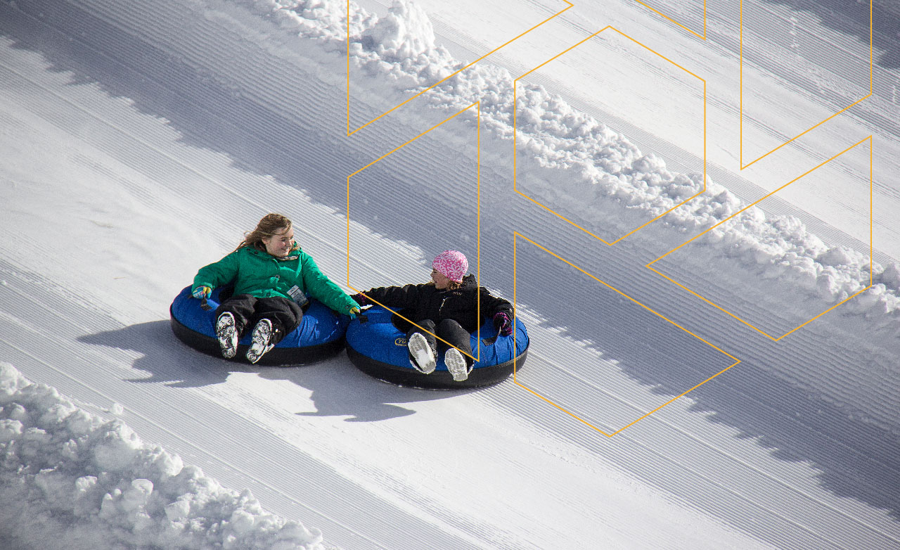 two young girls holding eachother's intertubes, tubing down a run at Mount Washington
