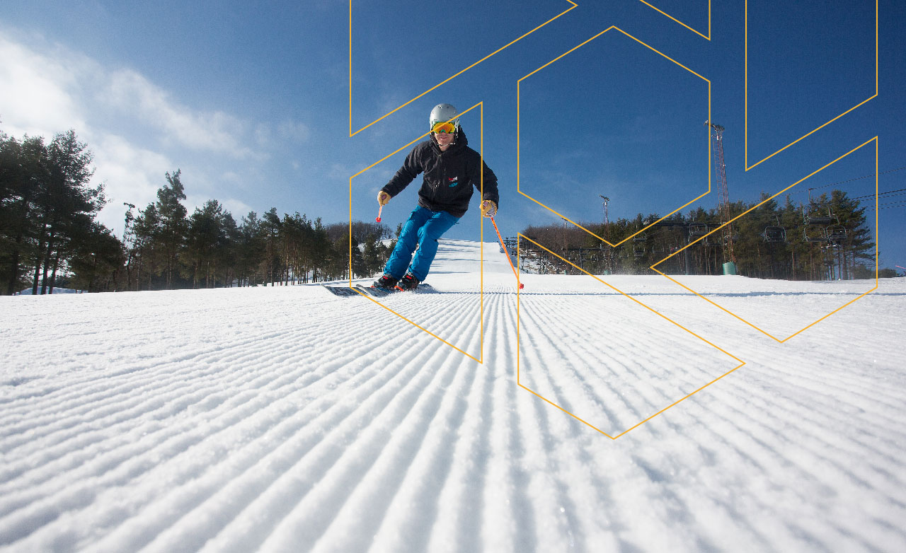 A ground level view of a Skier approaching you down a ski run at Wisp Resort.